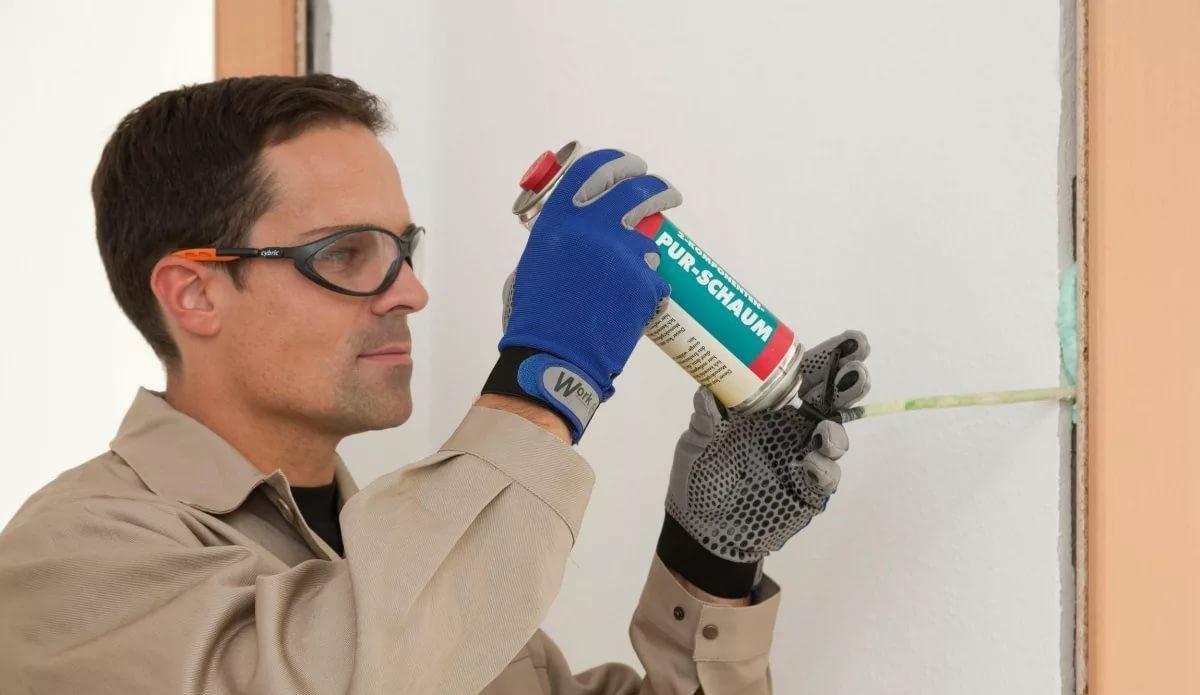 Мужчина в перчатках, очках и защитной одежде использует монтажную пену